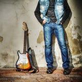 Penchement sur le mur avec une guitare électrique Images libres de droits