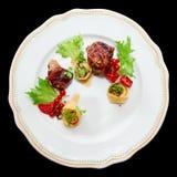 Penchez la viande avec des baies et des ravioli dans le plat, d'isolement Photos libres de droits