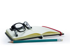 Pencil and black frame glasses on the notebook Stock Photos