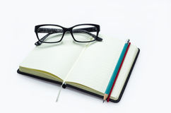 Pencil and black frame glasses on the notebook Royalty Free Stock Photo