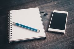 Pencil On A Blank Notebook Lying Next To A Business Smartphone On An Old Table. A Pencil On A Blank Notebook Lying Next To A Business Smartphone On An Old Table Stock Photo
