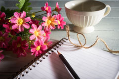 Pencil on book with flowers and coffee cup. Royalty Free Stock Photos