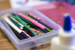 Pencil Box For School. Selective focus shot of pencil box with crayons markers pens and pencils. Glue bottle appears in foreground out of focus ** Note: Slight Stock Photo