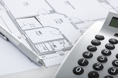 Pencil and calculator on blueprint of floor plan Stock Photography