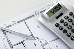 Pencil and calculator on blueprint of floor plan Royalty Free Stock Photography