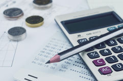 Pencil, calculator, coin and saving book on graph paper, saving. Concept Royalty Free Stock Photos