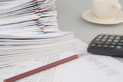 Pencil and calculator have blur cup of coffee as background. Brown pencil and calculator on finance account have blur pile overload document of report and Stock Image