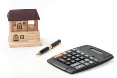 Pencil and calculator with wooden house Stock Photography