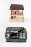 Pencil and calculator with wooden house Royalty Free Stock Photo