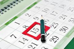 Pencil on the calendar with a bookmark on the date Stock Image