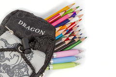 Pencil case. Black school pencil box with an inscription Dragon from which protrude pencils and pens Stock Photos
