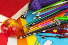 Pencil case contents scattered over a coloured card background Stock Photo