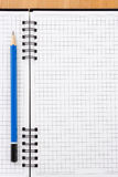 Pencil on checked notebook Royalty Free Stock Photos