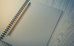 Pencil on checked notebook on wood background Stock Image