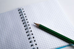 Pencil on the checkered paper exercise book Royalty Free Stock Image