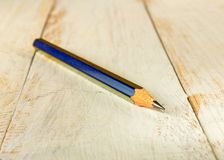 Pencil and chips on a wooden table Stock Images