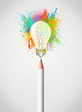 Pencil close-up with colored paint splashes and lightbulb Stock Photo