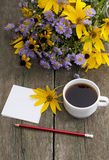 Pencil, coffee and bouquet of wild flowers Stock Photography