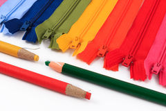Pencil and colorful zippers in different colors. Royalty Free Stock Image