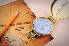 Pencil, compass and vintage map on a wooden table. Royalty Free Stock Image