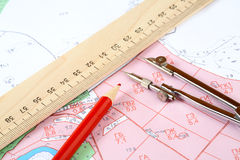 Pencil  compasses and  ruler on a topographic map. Red pencil  compasses and  ruler on a topographic map Royalty Free Stock Photography