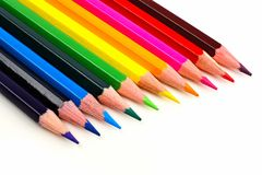 Pencil crayon close up. Row of colorful pencil crayons coming from corner over a white background Stock Images
