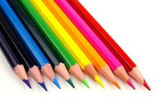 Pencil crayon close up. Row of colorful pencil crayons coming from corner over a white background Stock Photo
