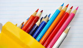 Pencil crayons box on lined paper. Royalty Free Stock Images