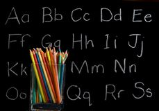 Pencil crayons with chalkboard background. Pencil crayons with chalkboard and letters in background Royalty Free Stock Photo