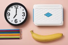 Pencil crayons, clock, banana and lunch box. High angle view of a clock at seven, some pencil crayons of different colors, a banana and a lunch box on a salmon Stock Image