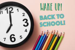 Pencil crayons, clock and text back to school. Closeup of a clock, some pencil crayon of different colors and the text wake up back to school on a pink Royalty Free Stock Image