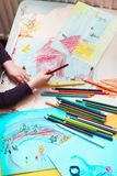 Pencil crayons scattered on desktop filled with colorful childlike drawings. Of playing children, house, car. Child hand holding pencil. Photo from above stock images