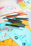 Pencil crayons scattered on desktop filled with colorful drawing. Pencil crayons scattered on desktop filled with colorful childlike drawings of playing children stock images