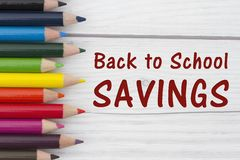 Pencil Crayons with text Back to School Savings. With weathered wood background Stock Photos