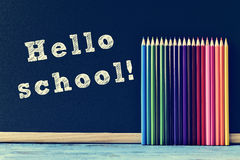 Pencil crayons and text hello school written on a chalkboard Stock Photography