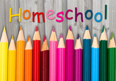 Pencil Crayons with text Homeschool. With weathered wood background Royalty Free Stock Images
