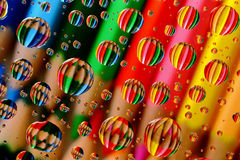 Pencil Crayons through Water Droplets (1). Colourful, aligned pencil crayons, reflected through random water droplets Stock Photo