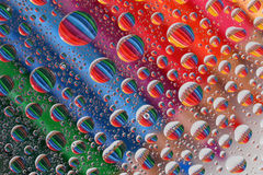 Pencil Crayons through Water Droplets (2). Colourful, aligned pencil crayons, reflected through random water droplets Stock Photos