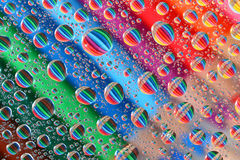 Pencil Crayons through Water Droplets (3). Colourful, aligned pencil crayons, reflected through random water droplets Stock Photo