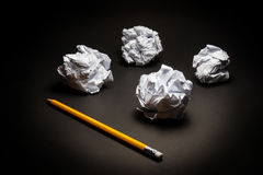 Pencil, crumpled paper on black background. Royalty Free Stock Photos