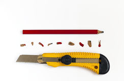 Pencil with cutter knife with shavings, on blank white sheet of Royalty Free Stock Photos