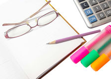 Pencil on a diary  with glasses, pens, highlighters and a calcul Stock Image