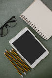 Pencil, digital tablet, spectacles and book arranged on chalkboard Stock Photo