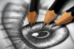 Pencil drawing. Close up of an eye drawing and three graphite pencils Royalty Free Stock Image