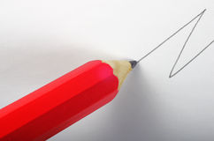 Pencil drawing line. A red pencil drawing a black zig zag line on a white paper following a diagonal direction Royalty Free Stock Photos