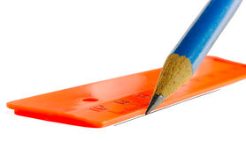 The pencil draws a line on a ruler. Orange ruler and dark blue pencil on a white background Stock Photos
