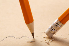 Pencil draws a wavy line on paper and pencil rubber eraser removing stripe. Business Breaking concept. Pencil draws a straight line on brown paper and pencil Royalty Free Stock Photography