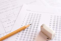 Pencil and eraser on answer sheets or Standardized test form wit. H answers bubbled. multiple choice answer sheet stock image