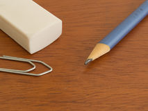 Pencil, eraser and clip on wooden table. Study and work materials Royalty Free Stock Photography