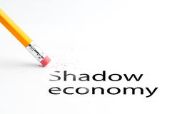Pencil with eraser. Closeup of pencil eraser and black shadow economy text. Shadow economy. Pencil with eraser Royalty Free Stock Photography